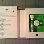 Inside of a 23andMe packaging spit kit. On the right of the box, there is text that outlines instructions on how to submit a DNA sample. On the left, there are tools.