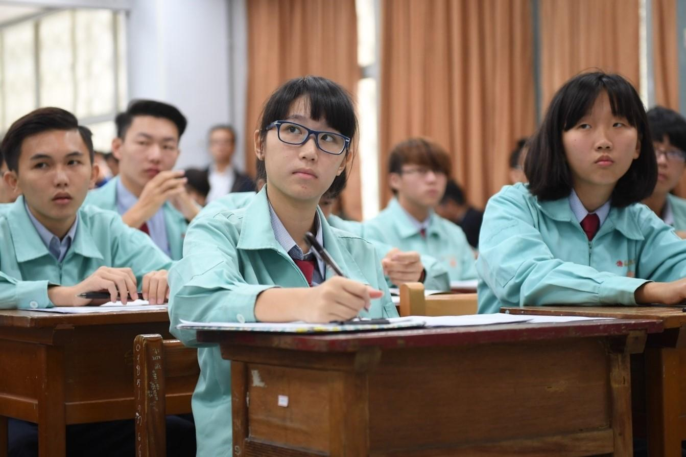 Rows of students wearing blue school uniforms sit at desks and take notes.