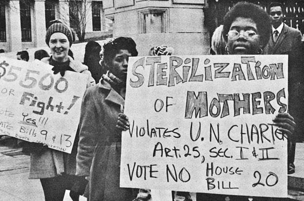 "A female, African American protester holds a sign that reads, ""Sterilization of mothers violates U.N. charter. Vote No on House Bill 20."""