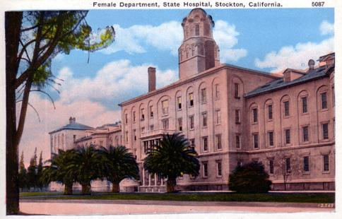 "Postcard from around 1910 with the title ""Female Department, State Hospital, Stockton, California."" Shows the front of a large pinkish building, four stories tall in the center with a tower, and two wings with three stories each. There are a few small palm trees and other trees in front of the building."