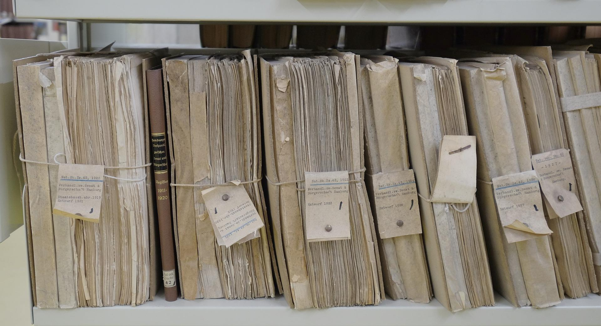 Several filing folders are placed side by side vertically. They have several papers stuffed into them, with old labels around the folder itself.