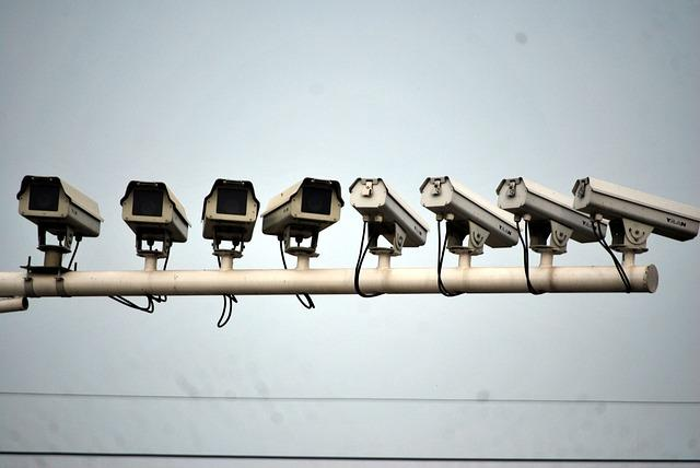 Several video surveillance cameras are lined up in different angles on a wall