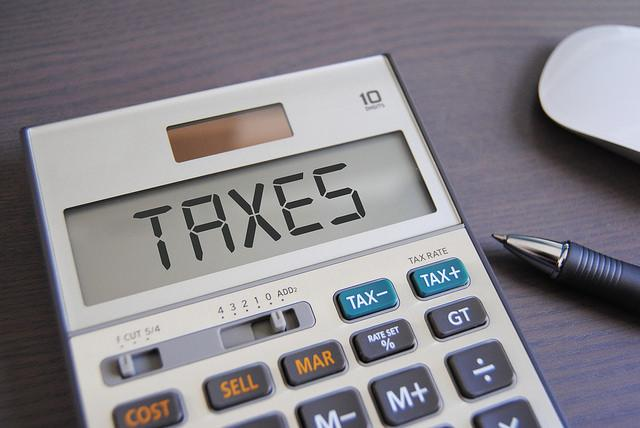 "A simple calculator reads ""TAXES"" on its screen. Beside the calculator is a ball point pen."