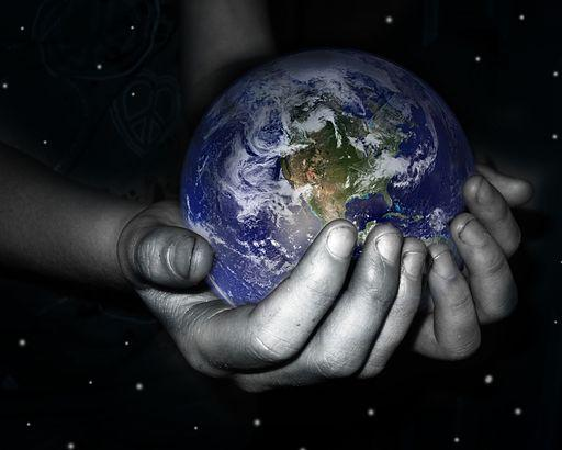 A grayscale image of a person's hand is shown, as it gently holds a colorful image of earth in their hands.