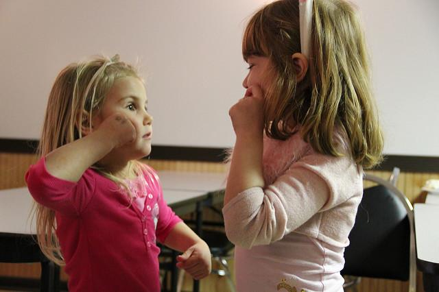 Two young girls face each other, and both appear to be using American Sign Language to communicate. They seem to be signing gum, candy, or apple.
