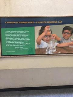 Image of a display from UC Berkeley Lawrence Hall of Science's Biotech Learning Lab featuring two children using a pipette and a beaker.