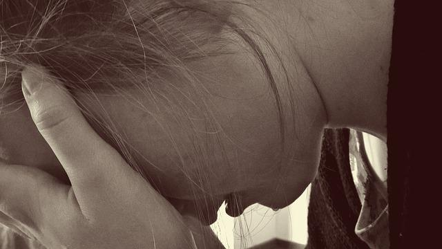 A person leans and covers their head, expressing sadness.