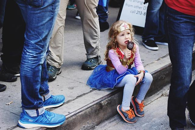 A little girl, dressed in a Wonder Woman's costume, sits on a sidewalk eating ice cream, while adults walk around her.