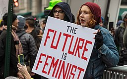 "Two women are pictured holding a protest sign stating, ""The future is feminist"""