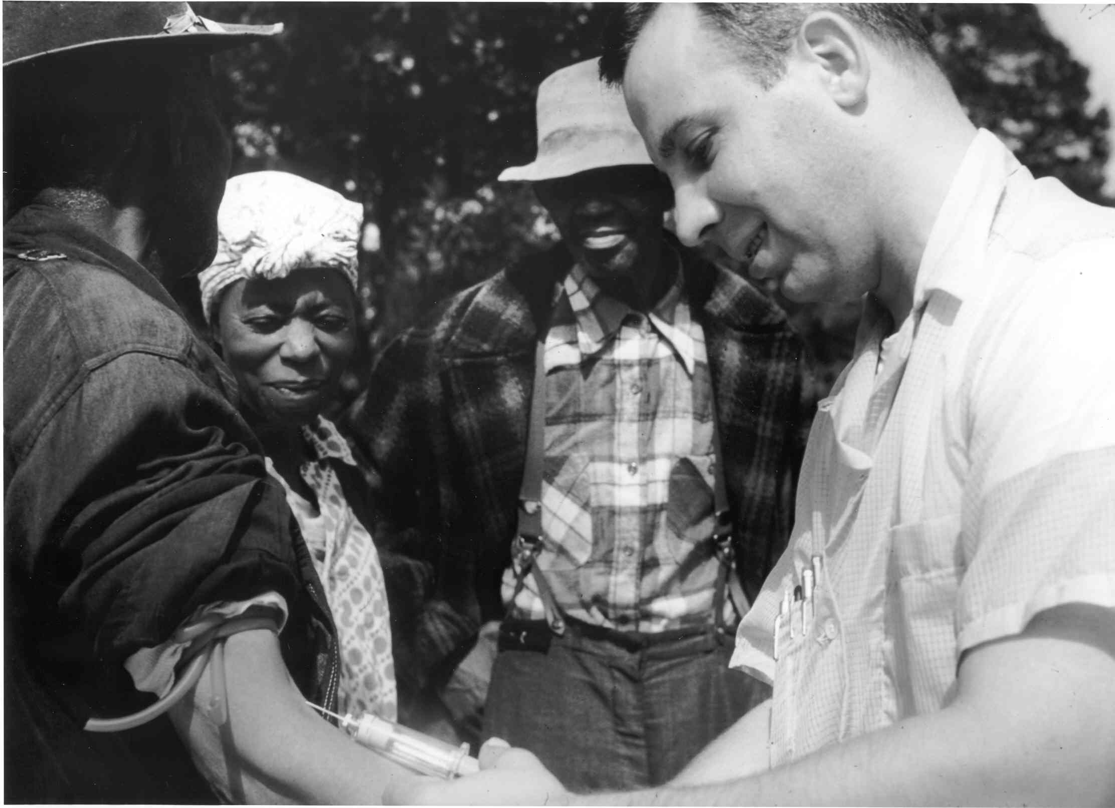 Archived black and white photo from the Tuskegee study. A white doctor draws blood from a black study participant with two others observing.