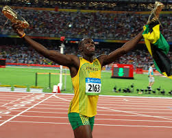 track star Usain Bolt holds up a flag after winning a race