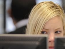 A blonde white woman looks suspiciously out of the corner of her eyes, onto a computer screen that is in front of her.