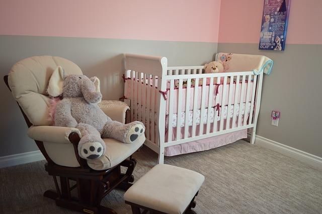A cradle and a rocking chair occupy a baby room painted pink.